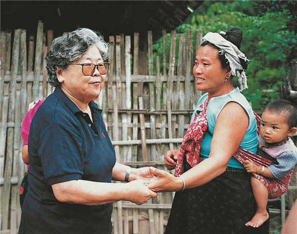 Η Λι (αριστερά) χαιρετά μια γυναίκα σε μια επίσκεψη στο χωριό Μαννανσίνγκ (Αναγέννηση), στην επαρχία Γιουνάν, το 1998. [Η φωτογραφία παρέχεται στην China Daily]